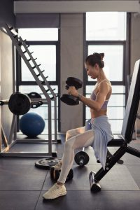photo of woman sitting while holding dumbbells